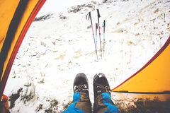 Feet Man relaxing view from tent camping. Entrance outdoor Travel Lifestyle concept snow mountains on background winter vacations Stock Photo