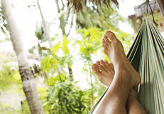Feet of a man resting in a hammock Stock Image