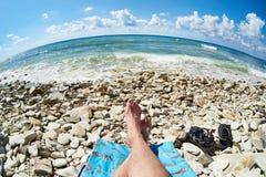 Feet of man resting and sunbathing on rocky beach Royalty Free Stock Photos