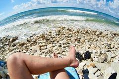 Feet of man resting and sunbathing on rocky beach Stock Photo
