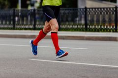 Feet man runner in red compression socks. Running on road royalty free stock images