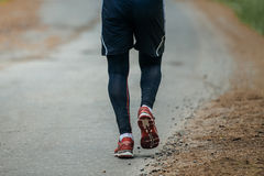 Feet man running down road. In woods during a marathon Stock Images