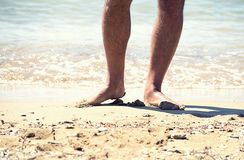 The feet of the man on the sand of the sea Stock Photography
