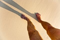 Feet of man with shadow at the beach Royalty Free Stock Image