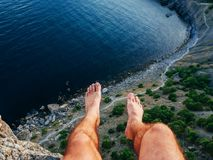 Feet of man sitting freely on high mountain nature over sea during summer vacation. Feet of the man sitting freely on the high mountain nature over the sea Stock Image