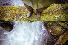 Feet Man standing on log over river outdoor Stock Photography