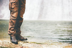 Feet Man trekking boots walking Outdoor. Travel Fashion Lifestyle waterfall and lake nature on background stock photography