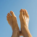 Feet of a man under  blue sky Stock Photography