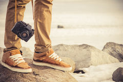 Feet man and vintage retro photo camera. Outdoor Travel Lifestyle vacations concept Stock Photos