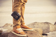 Feet man and vintage retro photo camera. Outdoor Travel Lifestyle vacations concept Royalty Free Stock Photos