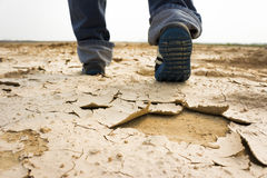 Feet of man walking on dry soil. And crack royalty free stock images