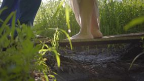 Feet of man and woman can't miss each other on the wooden bridge close-up. Girl walking barefoot. Country lifestyle. Connection with nature, rural life, flirt stock footage