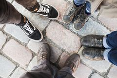 Feet of man, woman, teenager and child. Real family stands together in circle on cobbled street. Top view Stock Photos