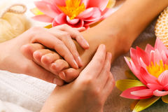 Feet massage. Woman enjoying a feet massage in a spa setting (close up on feet royalty free stock image