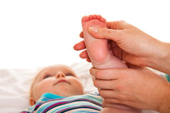 Feet massage of infant girl Stock Images