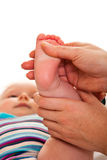 Feet massage of infant girl Stock Photos