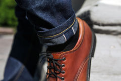 Feet of Men  in selvedge jeans and retro shoes Royalty Free Stock Image