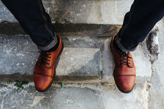 Feet of Men  in selvedge jeans and retro shoes Royalty Free Stock Photos
