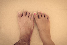 feet of men and women in the sea sand Stock Photos