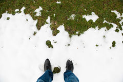 Feet in mens boots and jeans are in snow in front of green grass Royalty Free Stock Images