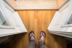 Feet of middle aged man standing in balcony door royalty free stock images