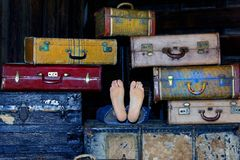 Feet in the Middle of Suitcases. Two feet sticking out of a stack of old antique suitcases Royalty Free Stock Photos