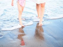Mom and daughter walking on beach. The feet of a mom with her daughter walking in the water on a sandy beach stock image