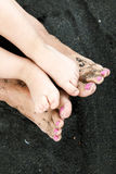 Feet of mom and toddler in the black sand close-up. Summer, beach and family concept. Mom and child relaxing on the unique beach Stock Image