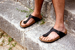 Feet of monk. Two Caucasian feet of a monk in black sandals standing on ancient stairs Stock Images