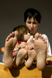 Feet of mother and child. Morning Stock Image