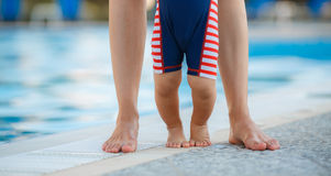 Feet of mother and child by the pool Stock Image