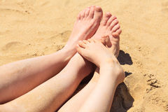 Feet of mother and her child in the sand Royalty Free Stock Images