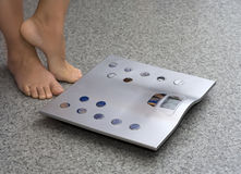 Feet near bathroom scale. On stone floor Stock Photography