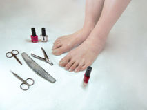 Feet need a pedicure. Legs with long nails and Tools for manicure(pedicure) on white background Stock Photo