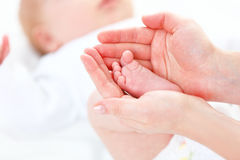 Feet newborn baby in arms him mother Royalty Free Stock Image