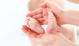 Feet newborn baby in arms him mother Stock Images