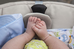 Feet of a newborn baby boy in  stroller Stock Images