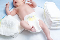 Feet of newborn baby on changing table with diapers Royalty Free Stock Photos