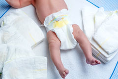 Feet of newborn baby on changing table with diapers Stock Photos