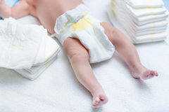 Feet of newborn baby on changing table with diapers Royalty Free Stock Photo