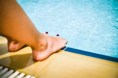 Feet next to pool Stock Image