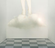 Feet not on the ground. Artistic surreal conceptual image that represent two human legs and feet under a cloud that fly away from a claustrophobic room Royalty Free Stock Images