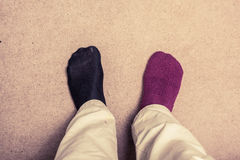 Feet with odd socks on  carpet. Feet with odd socks, one black and one purple, on  carpet Stock Photo