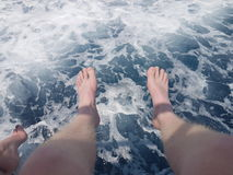 Feet off the boat. Dangling my feet off the side of the boat stock image