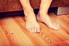 Feet of old woman on the floor stock images