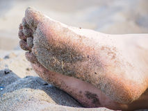 Feet of one unrecognizable caucasian person resting in sand. With wet sand on foot soles Royalty Free Stock Images