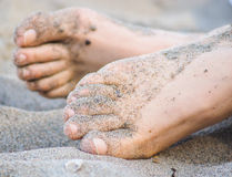 Feet of one unrecognizable caucasian person in sand. Feet of one unrecognizable caucasian person resting in sand, with wet sand on feet stock photo