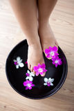 Feet in orchid spa bowl Stock Photos