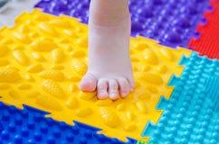 Feet on an orthopedic mattress. Little children`s foot on an orthopedic mat royalty free stock image