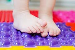 Feet on an orthopedic mattress. Little children`s feet on an orthopedic mat stock image